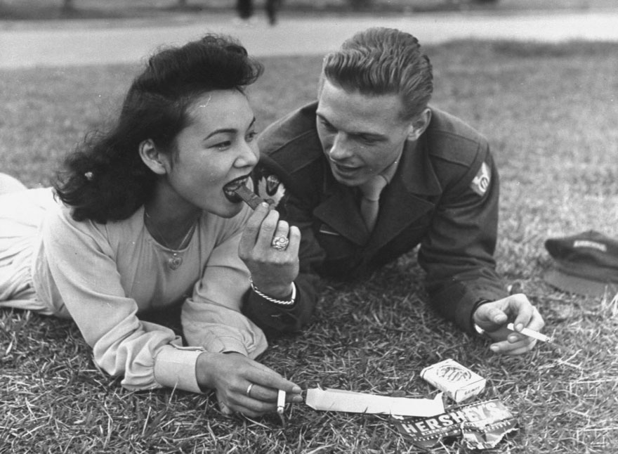 60 + 1 Heart-Warming Historical Pictures That Illustrate Love During War - Us Soldier And Local Girl Sharing A Chocolate Bar And Cigarettes, 1940s