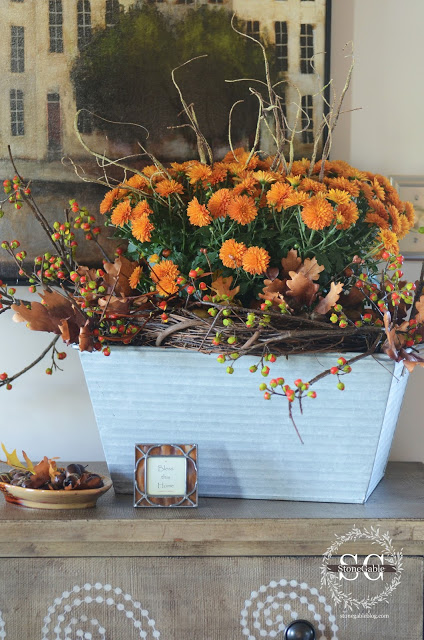 These orange flowers and rustic sticks are great for the fall season.