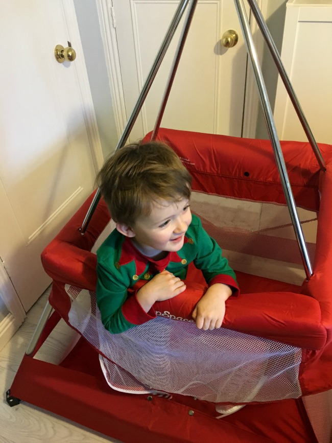 Babyhub-sleepspace-travel-cot-child-in-Elf-Christmas-pyjamas-standing-in-cot