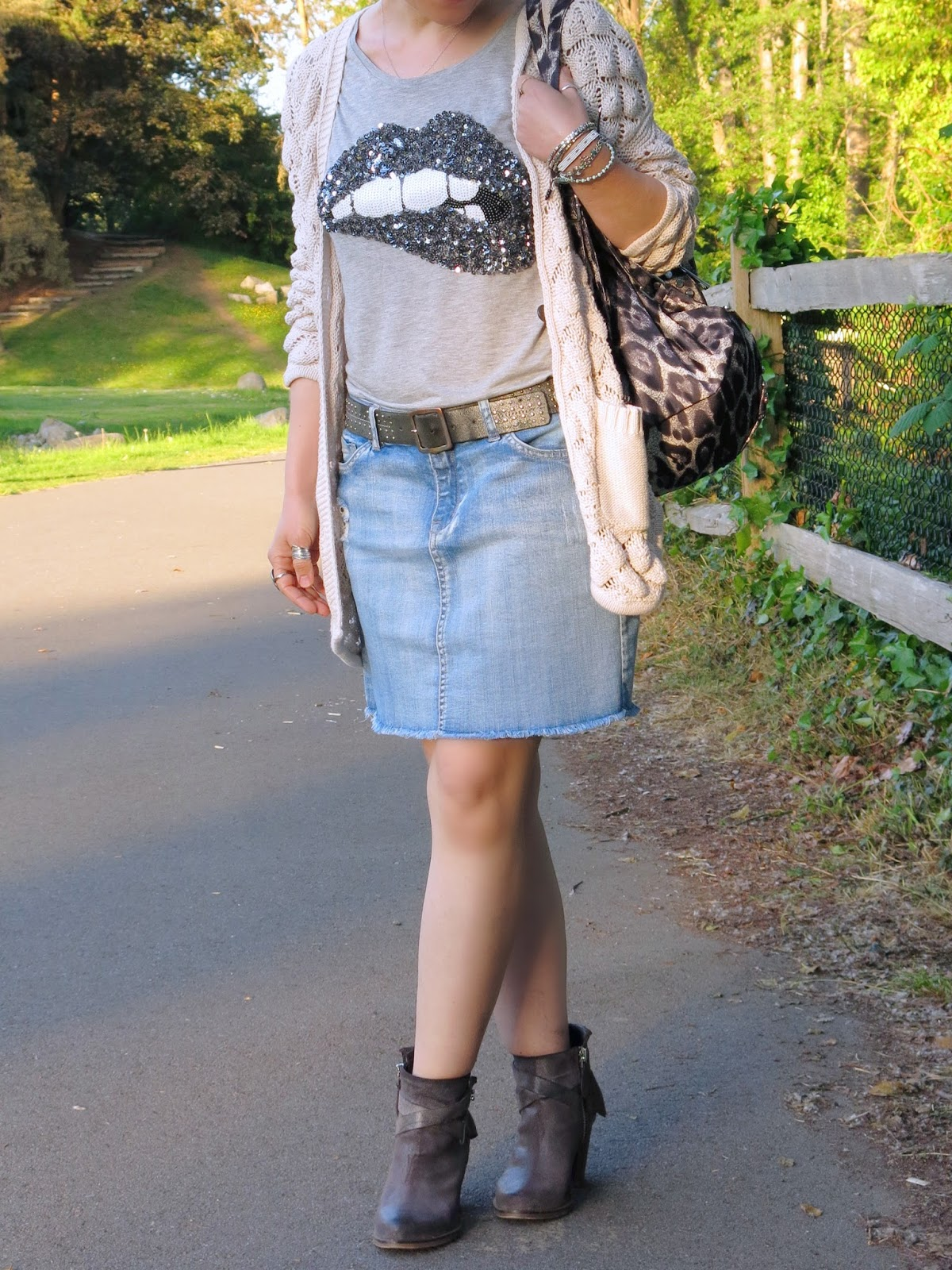 styling a sequinned t-shirt with a cut-off denim skirt, cardigan, and booties