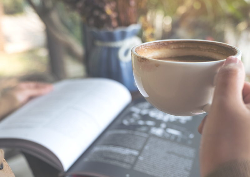Reading a book and drinking a coffee in the sun in a post about ten easy ways to simplify your life today