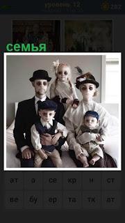 сидит семья в масках и фотографируется около окна