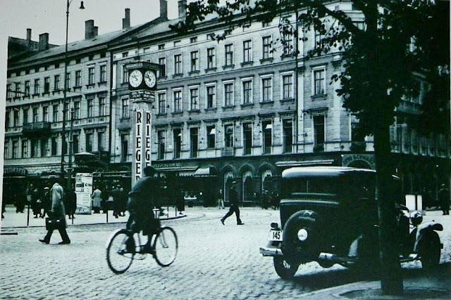 """1930-е годы. Рига. На углу бульвара Бривибас и Аспазияс. Часы с рекламой шоколадной фабрики """"Th. Riegert"""""""