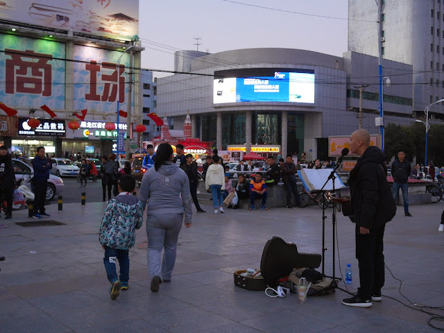 man signing and playing guitar at Culture Square in Mudanjiang, China