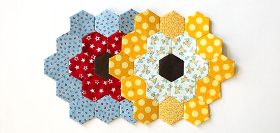 YTopview of two overlapping heaxagon flower quilt blocks, one in red and blue and the other in yellow and white, on a white background.