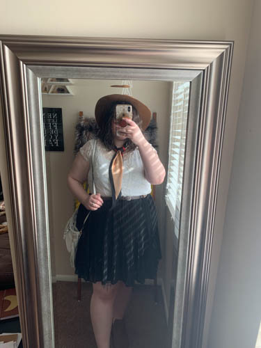 A mirror selfie of an outfit of a white lace blouse, a pink and black silk neck scarf, a black pleated skirt and black Chelsea boots.