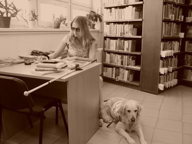 Linda sedí u stolu v knihovně, na stole leží knihy, lupy a bílá hůl. U stolu leží Cilka