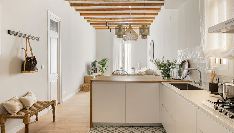 Cocina open concept abierta al salón con barra alta de madera