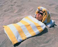 Bir kumsalda kendini kum içine gömerek kum banyosu yapan bir bayan