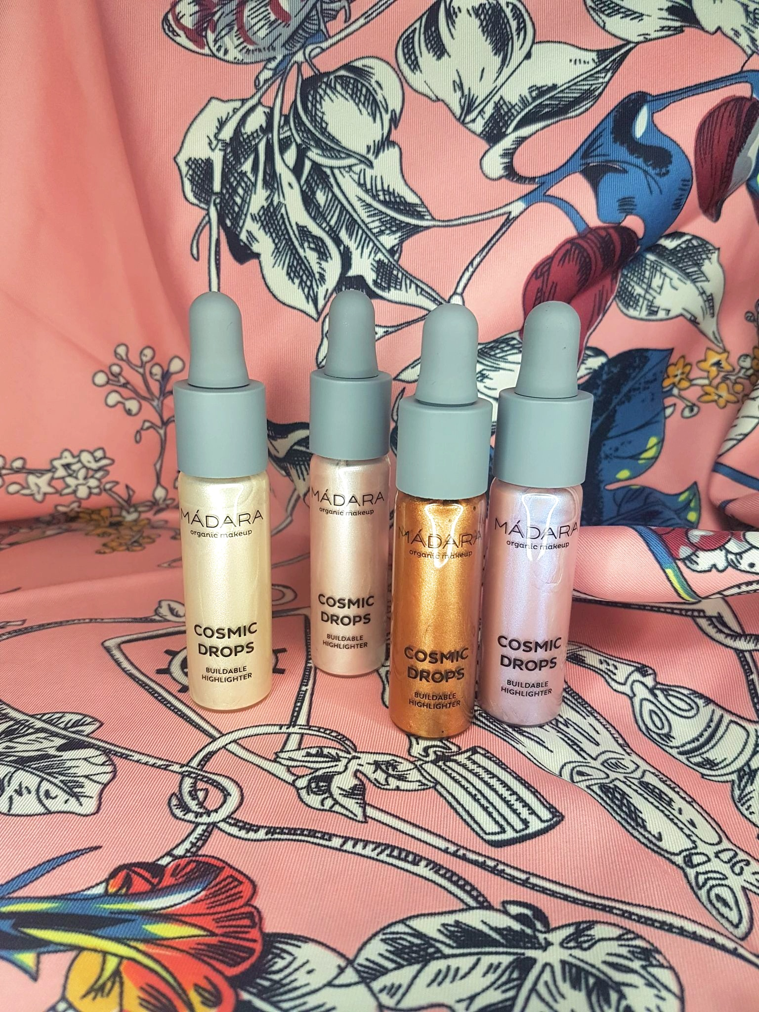 four shades of Madara Cosmic Drops lined up against a pink patterned silk. L-R: Naked Chromosphere, Cosmic Rose, Burning Meteorite, Aurora Borealis