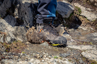 A close up shot of a Scarpa Zodiac Plus GTX boot stepping into a muddy puddle causing the water to splash.