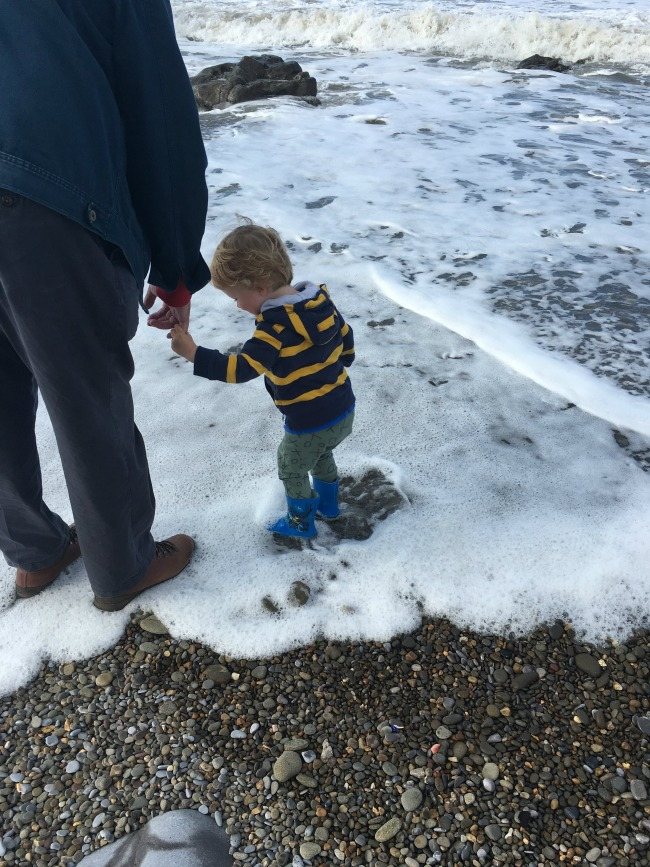 the-beach-the-bay-and-blowing-bubbles-toddler-standing-in-sea-foam