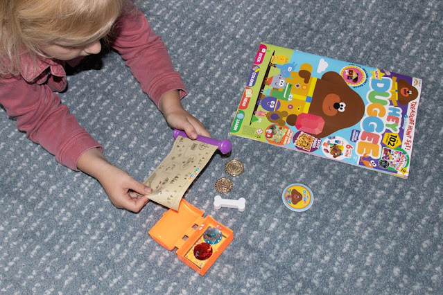 looking at the plastic tat that she loves which comes with the hey Duggee magazine