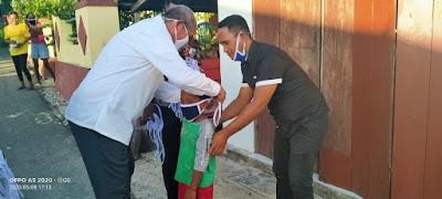 Bupati Malra M. Thaher Hanubun saat memakaikan masker kepada salah satu anak di Ohoi Ngilngof