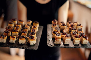 A woman holding a selection of wedding canapes on a black slate tray