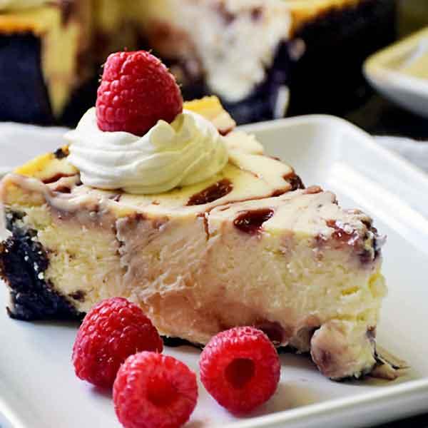 Slice of Raspberry White Chocolate Cheesecake on a white plate garnished with fresh raspberries