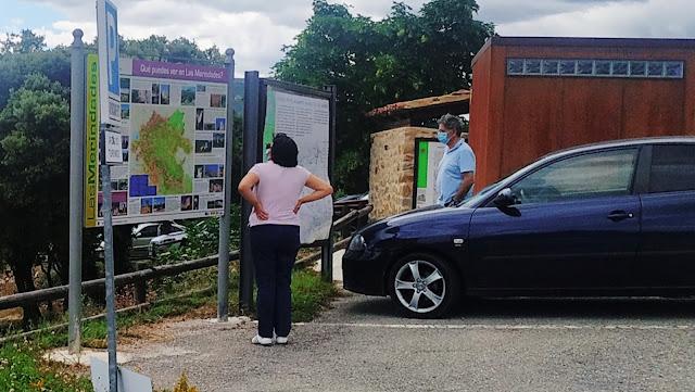 Turistas observan un panel informativo en Ojo Guareña.