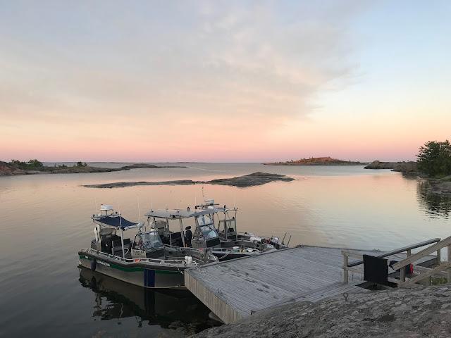 Kolme venettä laiturissa tyynellä merellä auringon laskiessa ulkosaaristossa