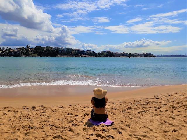 mulher de chapeu e biquini vermelho sentada em uma praia