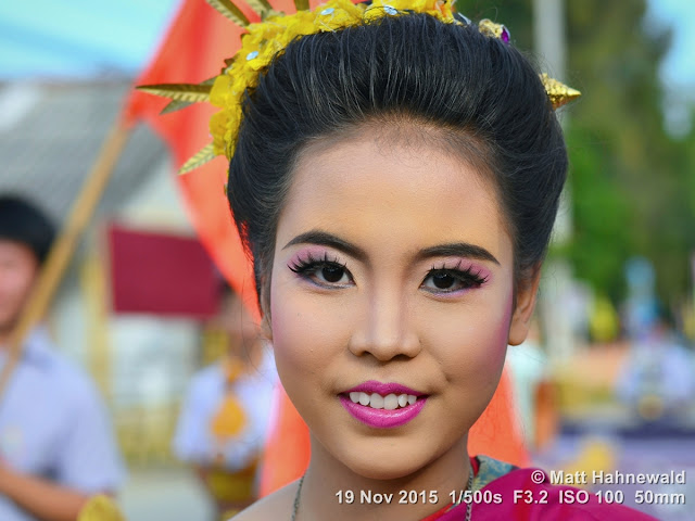Matt Hahnewald; Facing the World; Asia; Northern Thailand; Mae Chaem; people; closeup; portrait; street portrait; headshot; smiling; Thai girl; Thai smile; Land of Smiles; world cultures; travel; eye contact; Nikon DSLR D3100; 50 mm prime lens; colour; face; outdoor; street parade; make-up; beautiful; folk costume; Lanna tradition; dressed up to the nines; lip make-up
