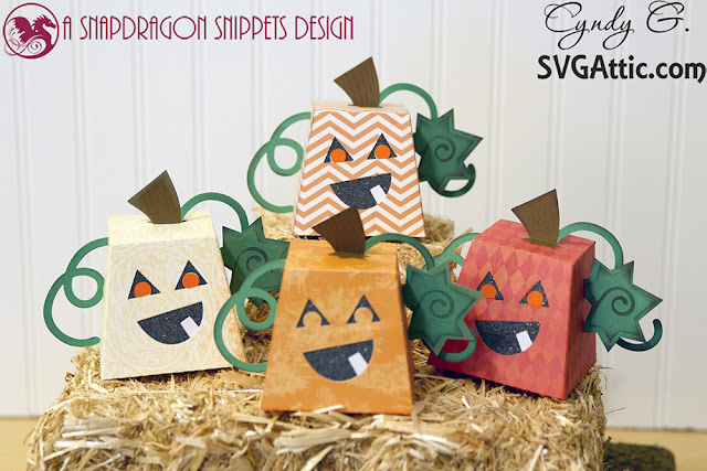 pumpkin treat boxes sitting on a bale of hay