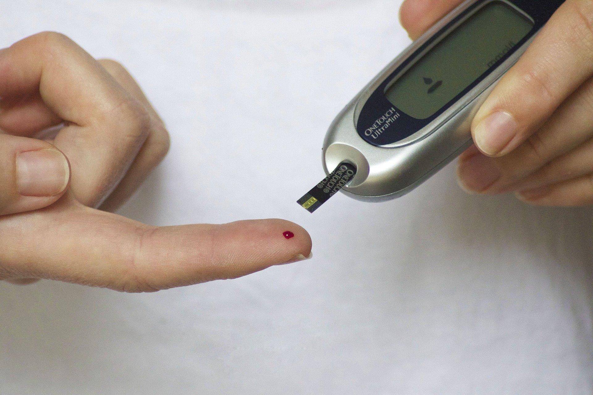 człowiek sprawdza poziom cukru nakłuwając palec