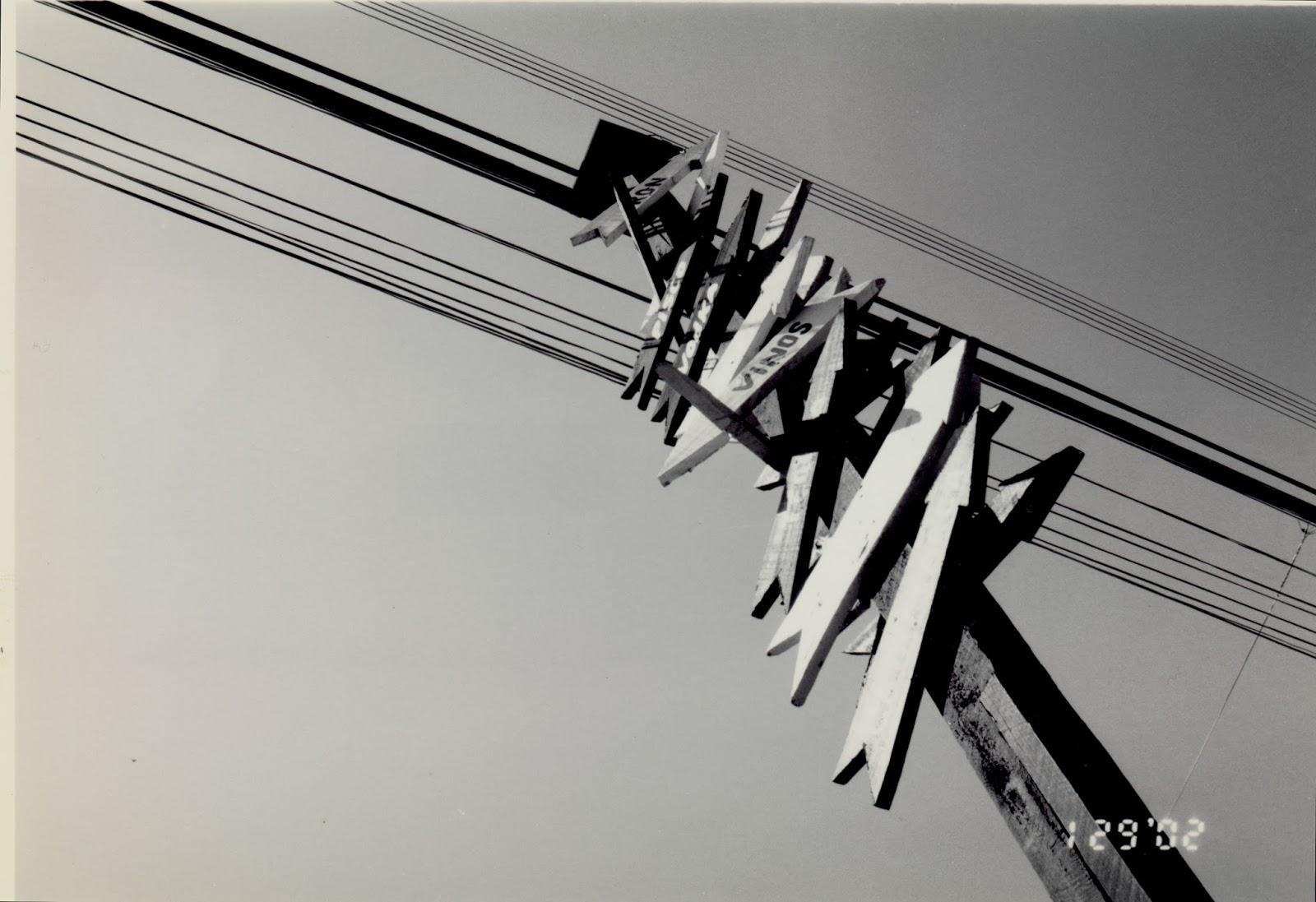 Poste de fiação com muitas placas apontando destinos diversos, em preto e branco: ilustra a seção a respeito dos textos das linhas de ''Chên / O Incitar (Comoção, Trovão)'', um dos 64 hexagramas do I Ching, o Livro das Mutações