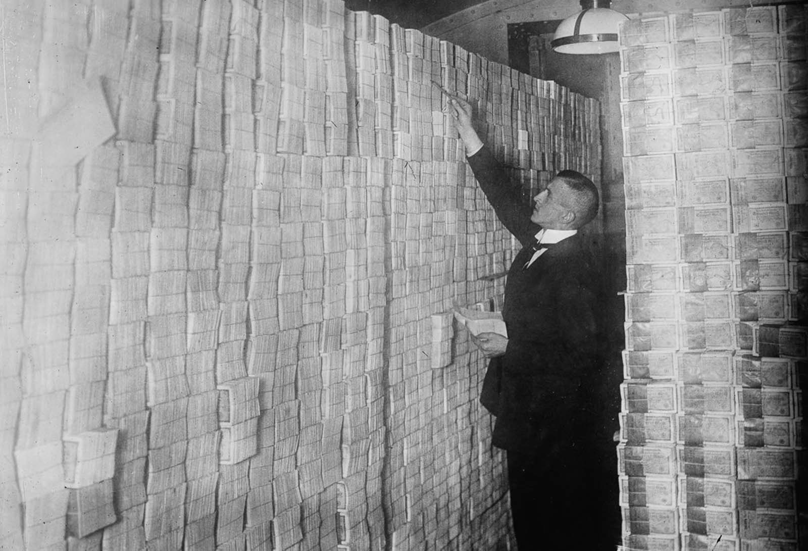 A Berlin banker counts stacks of bundled marks. 1923.