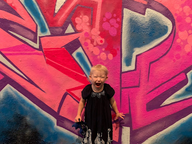A 3 year old roaring in front of a piece of grafitti in Leake Street London Waterloo