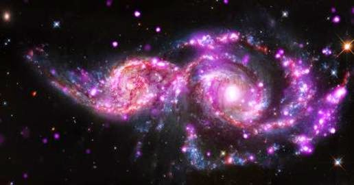 Composite image showing the collision between the galaxies NGC 2207 and IC 2163 with Chandra data in pink, the data optical light from the Hubble telescope is red, green, and blue (appears in blue, white, orange, and brown), and infrared data from Spitzer is red.