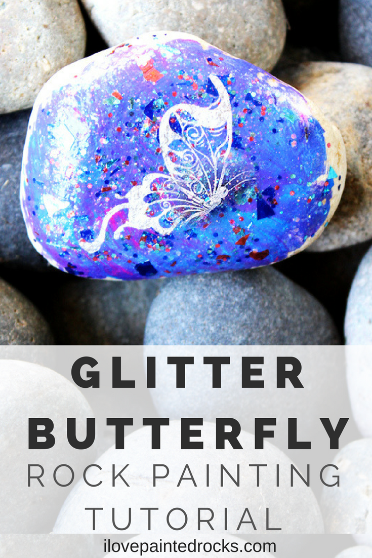 Rock painting tutorial: How to make a glitter butterfly painted rock. This is such a pretty rock painting idea! I l love the galaxy effect of the glitter together with the metallic butterfly from the temporary tattoo. #ilovepaintedrocks #rockpainting #paintedrocks #easycraft #kidscraft #rockpaintingideas
