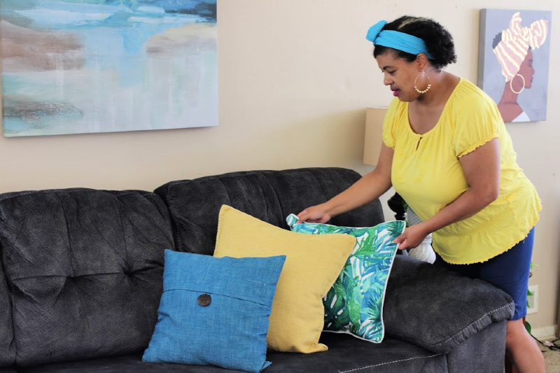 a woman adding summer pillows to her couch
