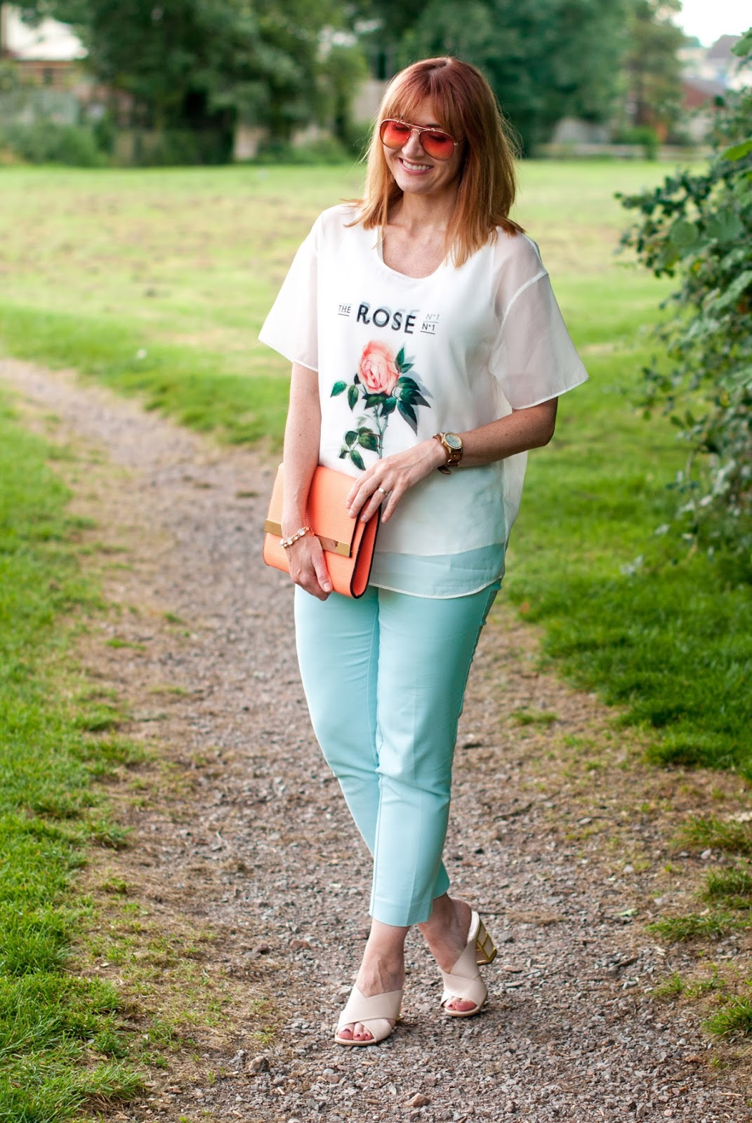 Soft whites and pastels summer outfit: Rose print sheer layered top mint trousers chinos pants nude crossover mules orange tinted aviators coral clutch | Not Dressed As Lamb, over 40 style
