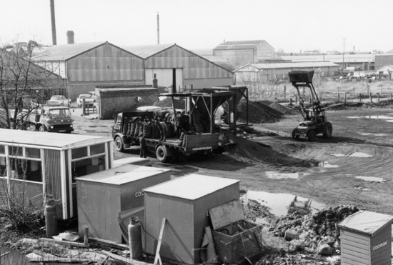 Photograph of Nash Bros coal lorries being loaded at Marshmoor sidings. Massils of Marshmoor, the furniture woodturners buildings are in the background. The huts of contractors working on the bridge are in the foreground. January 1972