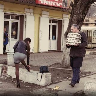 Foto em dia claro. À esquerda uma mulher jovem, em pé e de costas, cabelos castanhos compridos presos em rabo de cavalo baixo, jaqueta de couro marrom, saia cinza, curta e justa, meia calça preta transparente e sapatos de salto alto pretos. A mulher apoia a perna direita sobre uma mureta baixa de pedra enquanto ajeita o sapato próximo à bolsa de couro preto. Um homem observa a mulher enquanto caminha carregando uma pilha de sete cartelas de ovos. No chão, na direção do próximo passo, uma casca de banana. Ao fundo, fachada de um prédio, outra mulher em pé em frente a uma porta e mais além, parte de um troleybus.