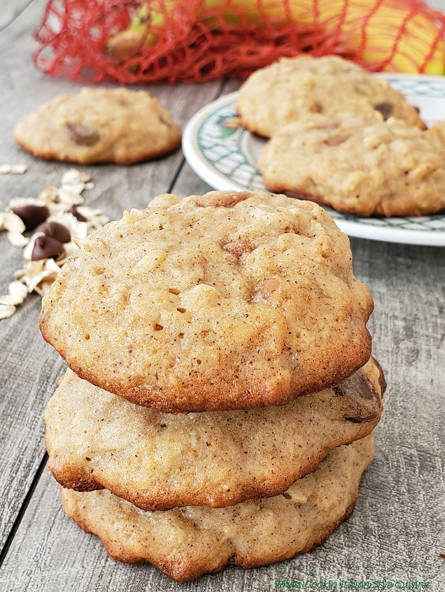 Banana cookies on a plate with bananas in a red netting in the background, chocolate chips and oatmeal on a grey board