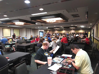 A view of the gaming hall. A long room full of tables, with lots of people at those tables playing a variety of games. At the far end, the games library can be seen.