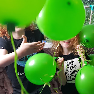 Bunch Of Balloons party pump review green balloons in air in front of grinning children