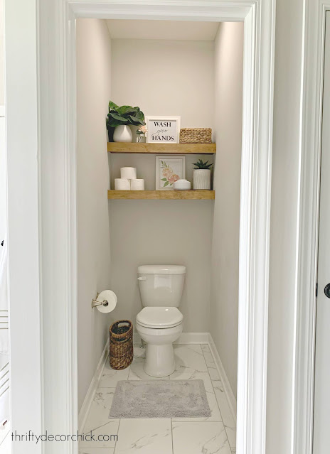 stained floating shelves above toilet