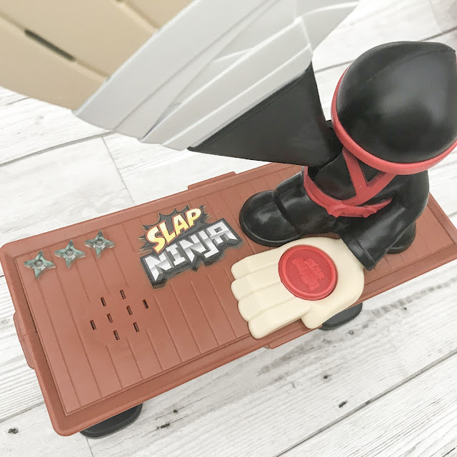 Unboxed toy ninja game with a large over sized hand with a chop action