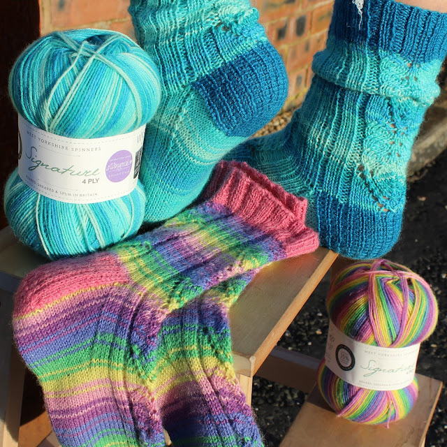 A ball of blue Seascape yarn and a pair of Adeline socks knitted in Seascape balanced on a wall, underneath is another pair of Adeline socks in Wildflower and a ball of Wildflower yarn