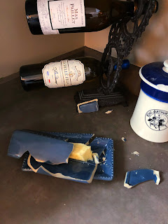 A shattered blue butter dish sits on the gray counter, behind is a wine bottle holder with 2 bottles and to the right is a King Arthur sour dough starter crock.