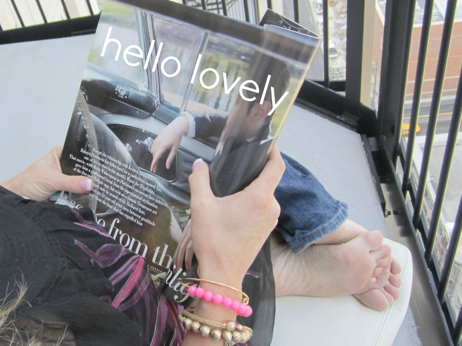 Woman on balcony wearing stylish bracelets and holding Hello Lovely magazine