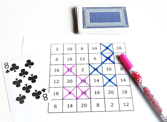 na zdjęciu wydrukowana plansza do gry z mnożeniem przez dwa, po lewej stronie leży karta osiem pik, po prawej stronie różowy pisak a nad planszą leży stos zakrytych kart