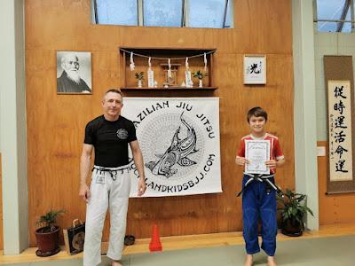 Professor Adam Evans with Finn earning his grey white belt