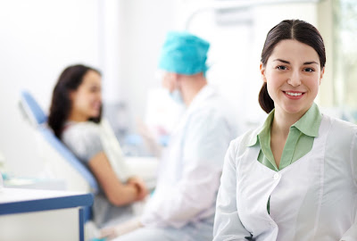 Nurse treating the patient in the background; happy nurse in forefront