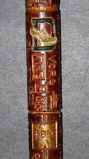 A close-up photograph of a cane with carvings on it.