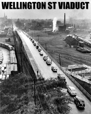 From a few storeys up, we see a raised roadway (and plank sidewalk alongside) cutting through railyards. Telephone poles carrying lines follow the left side of the viaduct, their tops below the camera. It extends from the lower right of the image (near present-day City Centre building) out to the distance in the upper left toward Hintonburg with the steeple of the St. Francis cathedral on the horizon. A line of 1930s cars is backed up the entire length of the bridge heading west (away from view) and one car is heading toward the camera. A single pedestrian is walkign on the boardwalk. The words WELLINGTON ST VIADUCT are written at the top of the image, as is Urbsite's wont.