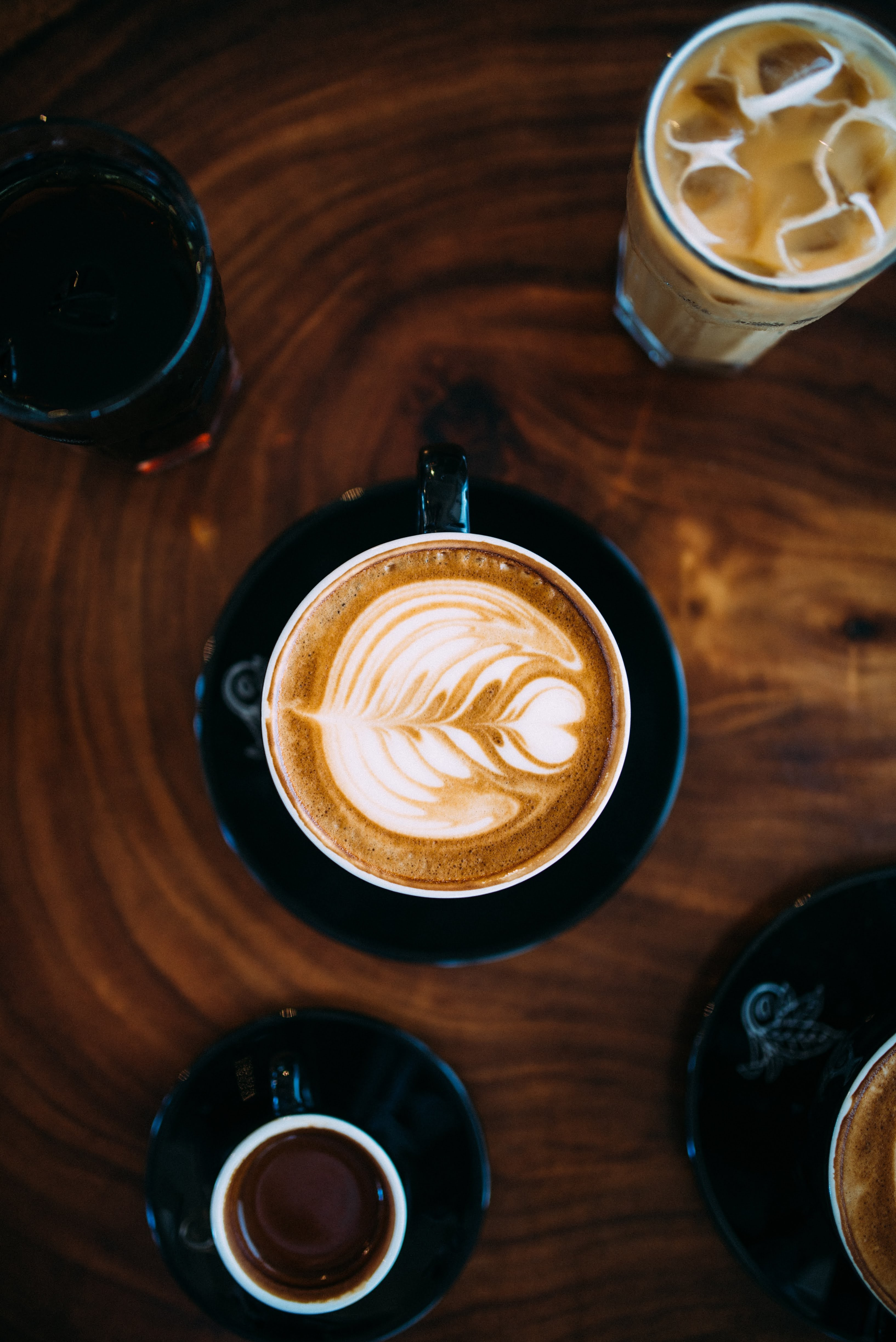 Coffee Cup with Milk Frothed on Brown Tabletop | Photo by Blake Wisz via Unsplash