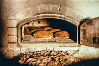 Kivisessä leivinuunissa paistuu pyöreitä ruisleipiä. Uunin luukku on auki.